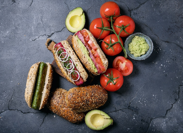 Vegeterian dog food served with tomatoes, avacado, onion and buns.